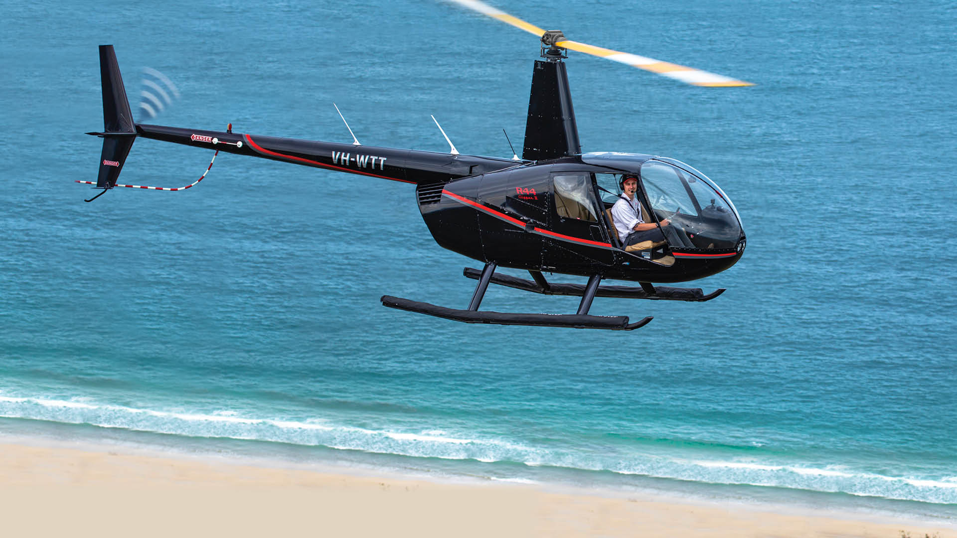 Morgan Vidler flying a helicopter over beach and water