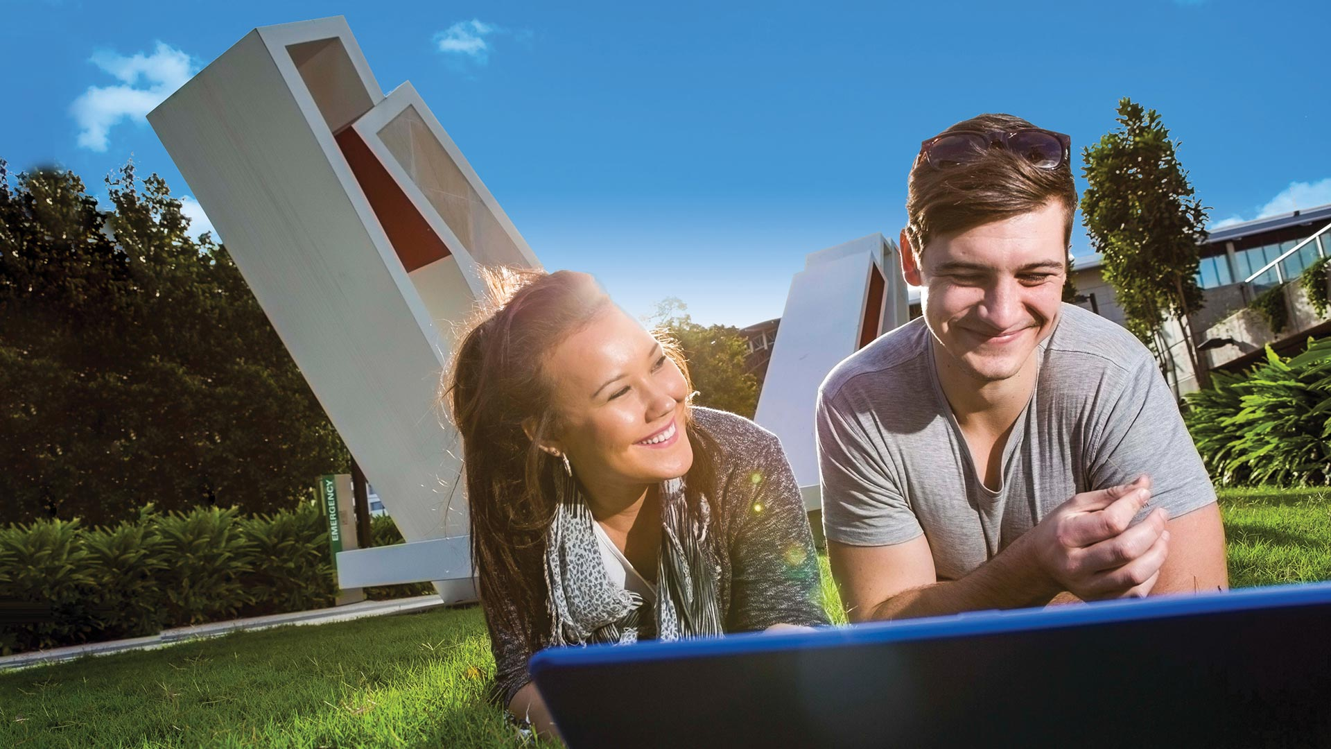generic-imagery-campus-girl-and-guy-laptop-smiling-on-greenspace-feature-1920x448.jpg